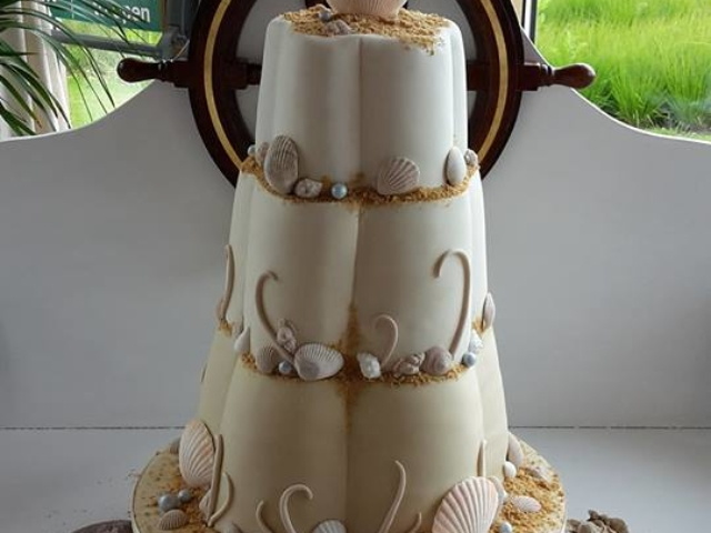 Sea themed wedding cake with edible shells, pearls and sand