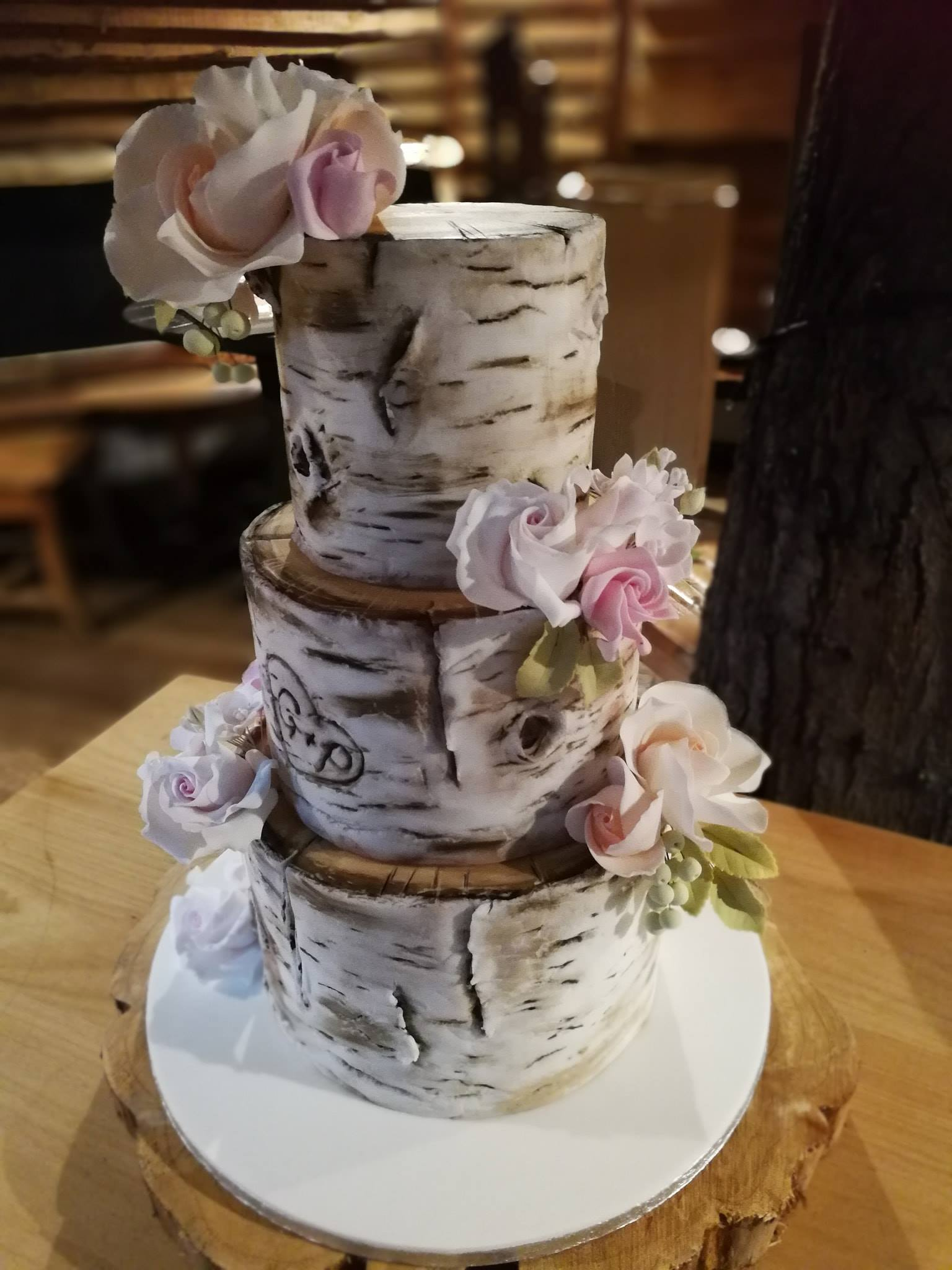 White Birch wedding cake with peach and pale pink sugar roses and green foliage